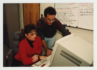 A man helps a woman with a computer
