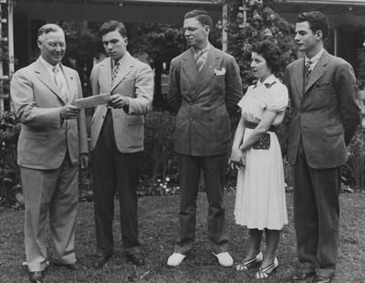 Robert Stilz, Lexington, President of the 1938 graduating class of the University of Kentucky, shown presenting to Marcus C. Redwine (left), Winchester, President of the University Alumni Association, a check representing 100% membership of the class in the organization.  At Stilz's left are Rankin Terry, Marion, Vice-president of the class; Mary Lou Stark, Lexington, class secretary, and Leon McCrosky, Harrodsburg, class treasurer; the location in Maxwell Place, the home of University President Frank L. McVey, where today he and his wife were hosts to several hundred graduates, faculty and friends of the University at their annual senior breakfast; taken from Lexington Herald-Leader