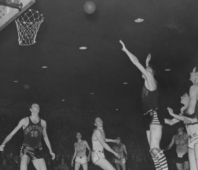 Basketball game action, UK versus West Virginia; Mel Brewer (15) watches as Milton Ticco (3) takes a shot; photo appears on page in the 1941 Kentuckian