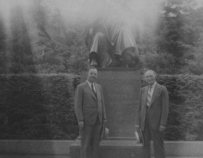 University President Herman Donovan (left) standing next to a former student of the class of 1876, J. E. Taylor (right) in front of the statue of President James K. Patterson