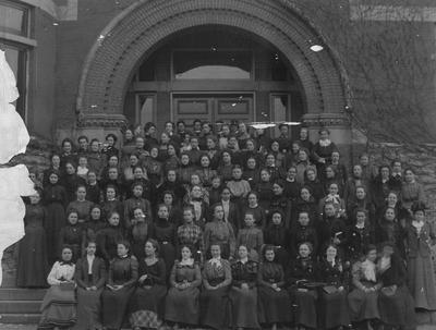 Large group photograph of unidentified women, titled Report of the Association of Alumni, 1990, page 11; gift of T. R. Bryant, July 28, 1948; taken in front of the Gillis Building (then the Chemistry and Experiment Station Building)