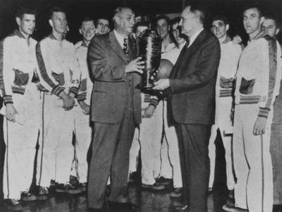 Basketball coach Adolph Rupp (right) and 1947-48 basketball team accepting the NCAA Championship trophy (players left to right: Jim Line, Dale Barnstable, John Stough?, Joe Holland, Alex Groza [obscured], Ralph Beard [obscured], Wallace