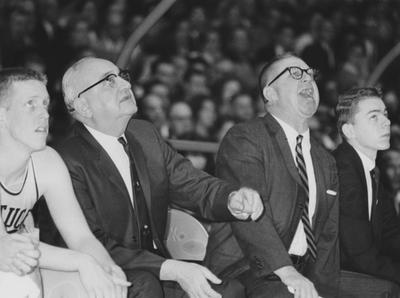 Basketball game action; photo of coaches Adolph Rupp (left) and Harry Lancaster from the bench; player Don Rolfes sits far left; man to the far right is unidentified