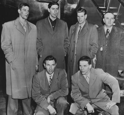Adolph Rupp and the five starters from the 1948-49 NCAA championship basketball team arrive in Seattle to play the title game against Oklahoma A & M; pictured (front, left to right) are Cliff Barker, Ralph Beard, (back, left of right) Wallace Jones, Alex Groza, Jim Line, Rupp; received from Cincinnati Enquirer, June 13, 1959, AP photo