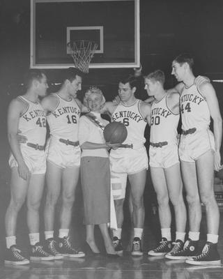 Basketball team members Lou Tsioropoulos (16), Cliff Hagan (6), Frank Ramsey (30), Phil Grawemeyer (44), and Bill Evans (42) pictured with Madge Barnett