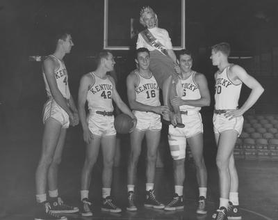 Basketball team members Lou Tsioropoulos (16) pictured holding Madge Barnett on his shoulders, standing with Cliff Hagan (6), Frank Ramsey (30), Phil Grawemeyer (44), and Bill Evans (42)