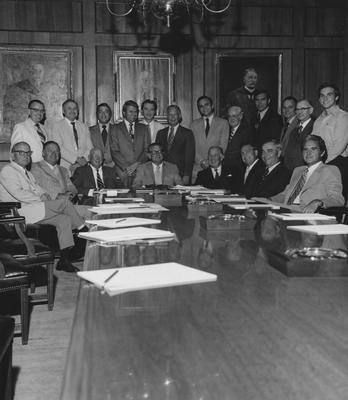 Athletics Board meeting; former governor A. B. Chandler sits to the left of University President Otis Singletary (4th from left), Cliff Hagan (standing 4th from right), Larry Forgy (standing 6th from right), Daniel Reedy (standing 3rd from left), Harry Lancaster (seated 2nd from left), and 14 other unidentified members