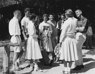 Three unidentified UK female cheerleaders and seven unidentified male cheerleaders during the Bull Session at YM camp; photographer:  University of Kentucky
