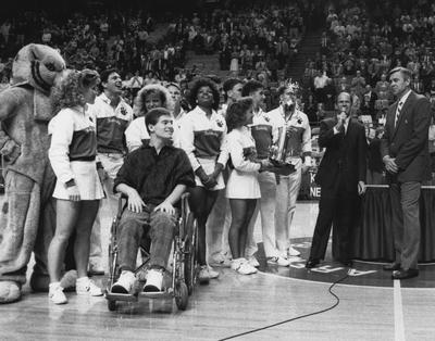 Presentation of the National Championship trophy to Dale Baldwin (in wheelchair) and rest of the 1986-87 team; athletics director Cliff Hagan is at far right