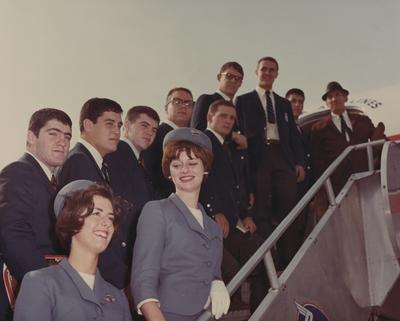 Members of the football team boarding a Delta Airlines plane; head coach Charlie Bradshaw is far right, wearing hat