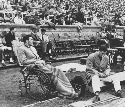 Basketball team member Wallace Jones sits in a wheel chair on the sideline, after having an appendectomy, of the UK versus Alabama football game, 1947; photo appears on page 199 in the 1948 Kentuckian