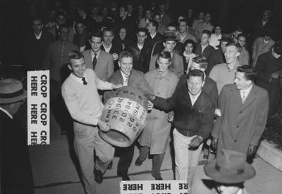 Unidentified students carrying the beer barrel trophy, which was won back after UK's victory over Tennessee, score 27-21; photo appears on page 44 in the 1965 Kentuckian