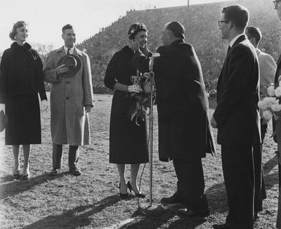 Mrs. Frank Dickey (far left), UK President Frank Dickey (2nd from left) and other unidentified people are watching UK Trustee and former Governor A. B. Chandler kiss the unidentified Homecoming Queen at Stoll Field; photographer:  University of Kentucky