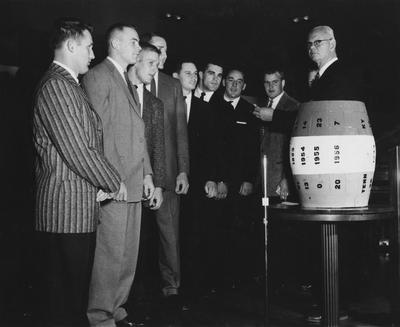 Several members of 1957 UK football team pictured with Athletics Director Bernie Shively, far right and the beer barrel