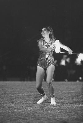 Unidentified majorette, using flaming batons, during band routine on the football field; game unidentified