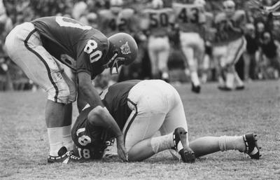 Unidentified football player helping another injured player during 1968 game. Photo appears on page 219 in the 1969 Kentuckian