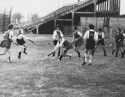 Unidentified field hockey players during a game against Eastern State College, near Stoll Field in 1960; photo appears in 1960 Kentuckian, page 245. Received December of 1960 from Public Relations
