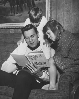 Former UK basketball player and Athletics Director Cliff Hagan pictured reading to his children; photo taken when Hagan was player/coach of the Dallas Chapparals of the now-defunct American Basketball Association; Dallas Morning News staff photo, Jo Ball, photographer