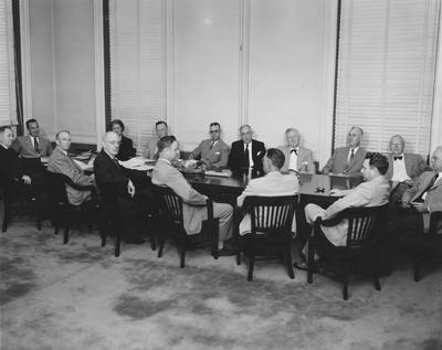 University of Kentucky Board of Trustees, 1952, in Administration Building boardroom including Governor Lawrence Weatherby and UK President Herman Donovan both seated at the far left end of the board table; other names of individuals listed on photograph sleeve