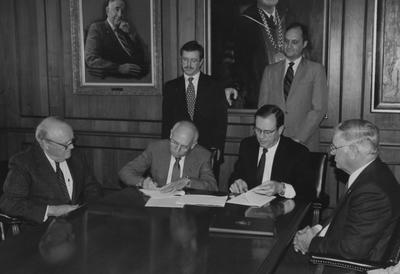 University President Charles T. Wethington, former Kentucky Governor Ed Breathitt (far left), Vice President Ben Carr (standing, right) and other members of the University of Kentucky Board of Trustees meet in the Administration Building boardroom