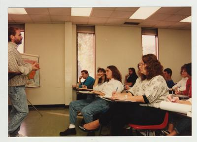 Students listen as a male professor listens in a classroom