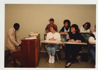 Students listen as a male African - American professor plays the piano in a classroom