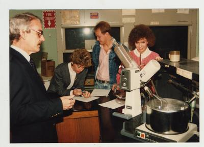 A male professor and his students look at a machine in a laboratory