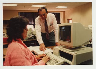 A male professor helps a female student in a computer class