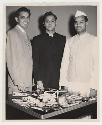 University of Kentucky students celebrate the 10th anniversary of the Republic of India's independence; Shown looking at an exhibit of handmade Indian objects are from left to right: Kann Shah, a former University of Kentucky student working in Lexington, and UK students Satish Chand Markanda and Govind Khandanpur