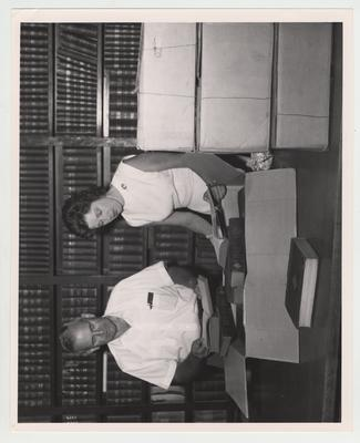 Wesley Patterson Garrigus (left), professor of Animal Husbandry, and Mary Powell Phelps (right) unpack books in the Agricultural Experiment Station Library