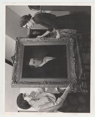 Jacqueline Bull(right), Director of Special Collections and Archives, and an unidentified woman (left) hold the portrait of Governor John White Stevenson given to the University
