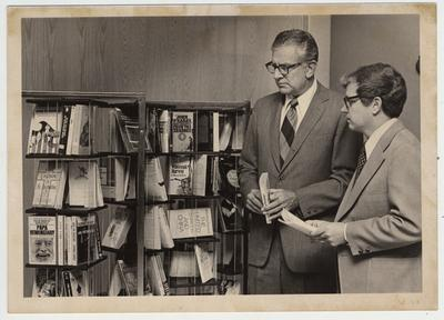 University of Kentucky President Otis A. Singletary (left) and Paul A. Willis, Director of UK Libraries, look at a paperback collection in the Margaret I. King Library of popular works, best sellers, and classics; Dr. Singletary originated the idea for the collection and his office provides funds for the books