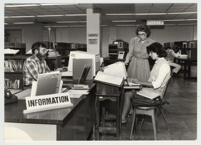 Norma Jean Gibson (woman standing with glasses), reference librarian, helps a female student in the Reference Area on the first floor of the Margaret I. King Library; This image was submitted for use in the 1983 / 1984 O. C. L. C. Annual Report