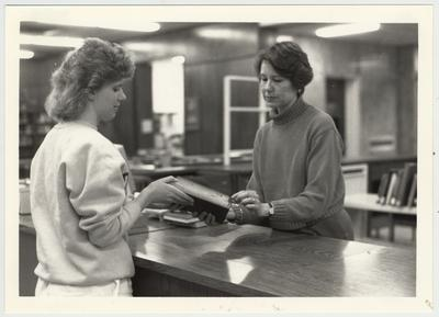 A student hands a book to librarian Judy Brown (right)