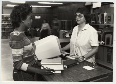 A student checks out a book from the library; Submitted for use the the 1983 / 1984 annual Report
