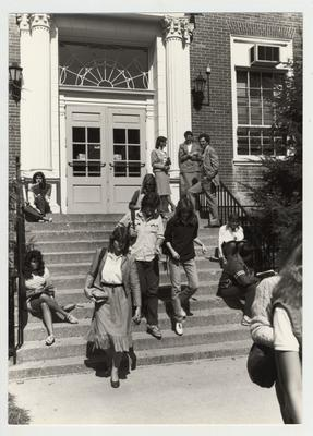 Students and staff on the steps of McVey Hall; Mike Lach stands top right; Submitted for use the the 1983 / 1984 annual Report