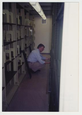 Bill Marshall replacing a shelf in the core stacks after it was cleaned and preparing for the move to the 1929 Margaret I. King Library