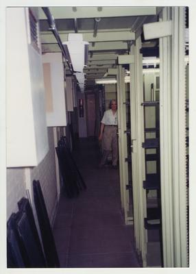 Cheryl Jones working hard to clean the shelving in the core stacks