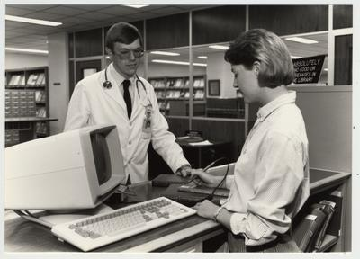 A woman checks out books to a male student in the Medical Library (located in Medical Center)