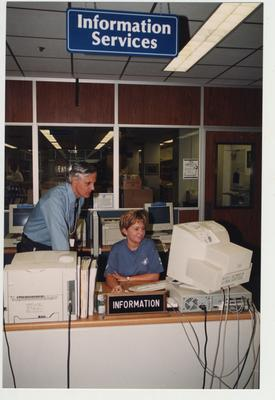 A man and woman look at a computer behind the Information Services desk in the Medical Library (located in the Medical Center); Photographer: Mark Minor