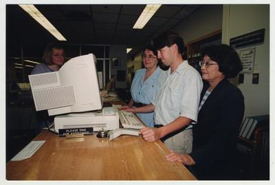 Librarian In Soon Chi (right), with an unidentified man and woman, standing behind the circulation desk looking at a computer and helping a female student in the Medical Library (located in the Medical Center); Photographer: Mark Minor