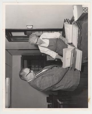 Professor Bennett Wall and Mrs. Thomas Underwood examine scrapbooks of Mrs. Alben Barkley