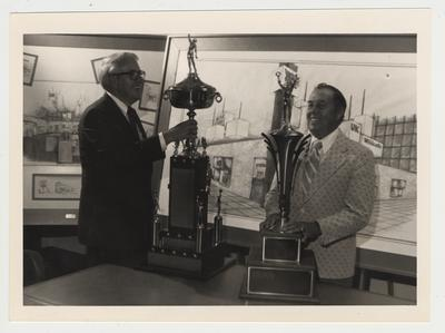 Charles Atcher and Cecil Bell with two trophies at the Adolph Rupp museum; Photographer: Jim Host & Associates