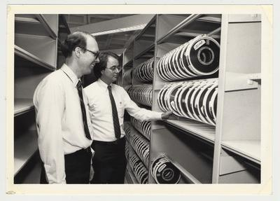 Frank Stanger and Terry Birdwhistell of the University Archives and Records Program division view the computer center back-up tapes which were stored in the library's area