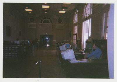 The Great Hall / Research room on the second floor in Margaret I. King Library (built in 1931); Frank Stanger is seated at the reference desk and Claire McCann is standing