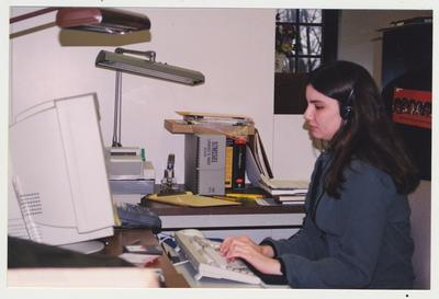 A female student typing at a computer in the Wendell Ford Center