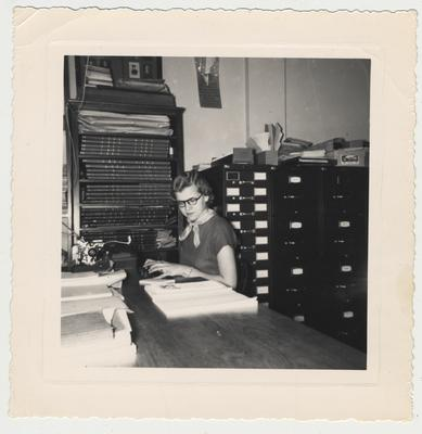 Winifred Lewellen at the typewriter typing the last page of the alphabetical list of WWII Kentucky War Dead; Office located on the fifth floor of King Library