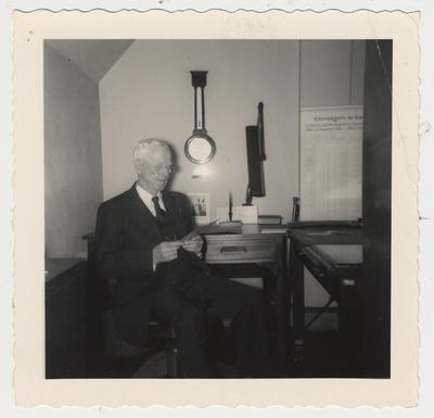 Professor Ezra L. Gillis, University Archivist, at his desk on the fifth floor of King Library with the barometer given to him by the Registrar's Association