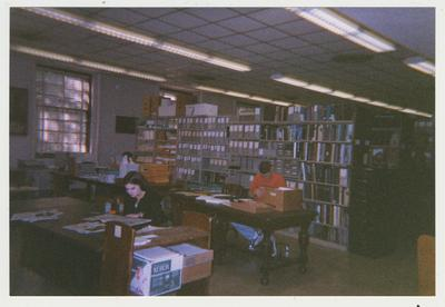 Room 204 in the Margaret I. King Library, University Archives processing area; Seated at the front tables are Becky Eaton and Patrick Honaker