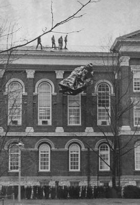 Administration Building, workmen on roof clearing away wind-damaged sections; Public Relation photo